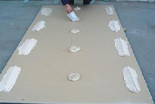 Нанесение клея на лист гипсокартона
